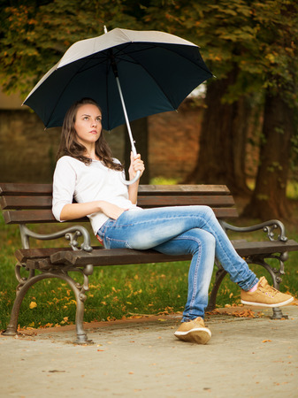 Lonely woman with umbrella sitting on the bench in the park. photo