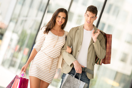 happynes: Young happy couple in shopping passes in front of window shopping mall carrying bags in their hands.