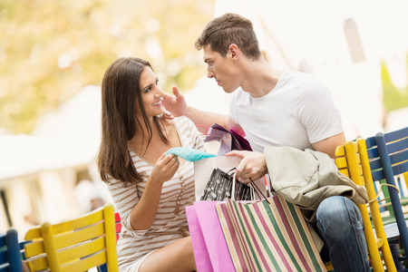 Young couple in the break after shopping at outdoor cafe watching the things they bought. Stock Photo