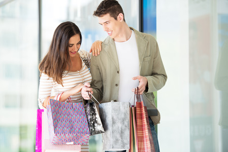 happynes: Young happy couple in shopping passes in front of window shopping mall carrying bags in their hands, looking in shopping bags.