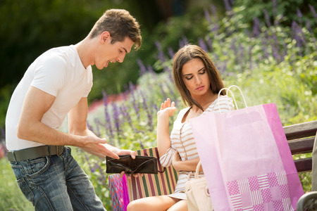 unnecessary: Young man yelling at his girlfriend in the park because of the money spent on buying unnecessary things by showing her his empty wallet.