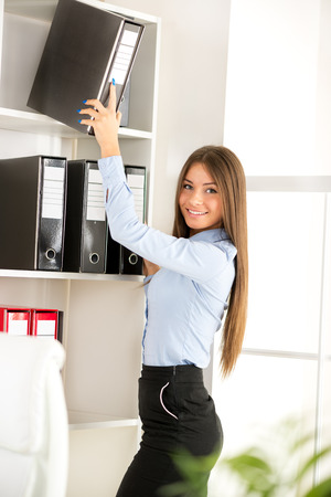 agrees: Beautiful Businesswoman agrees document in the office. Looking at camera.