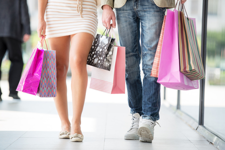 Legs of a young couple walk through town after shopping, while next to them are shopping bags.