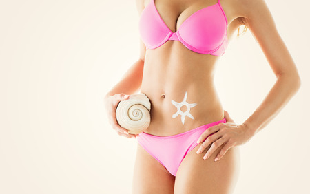 thin shell: Perfect Woman body in a bikini with sun-shaped sun cream and shell. Close-up. Stock Photo