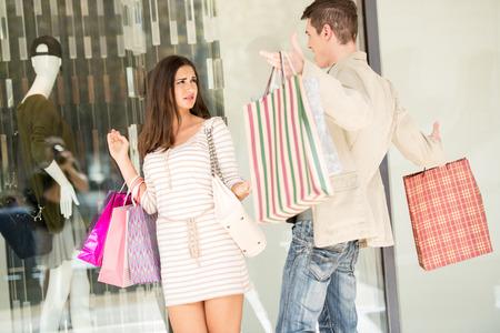 angry couple: Hombre joven rega�ar a su novia delante de la ventana de la tienda para gastar dinero en compras, llevando en sus manos un mont�n de bolsas de la compra. Foto de archivo