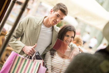 happynes: Young happy couple in shopping passes in front of window shopping mall carrying bags in their hands, looking in shop window.