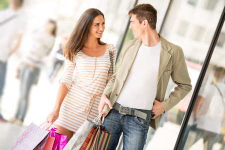 happynes: Young happy couple in shopping passes in front of window shopping mall carrying bags in their hands, looking at each other.