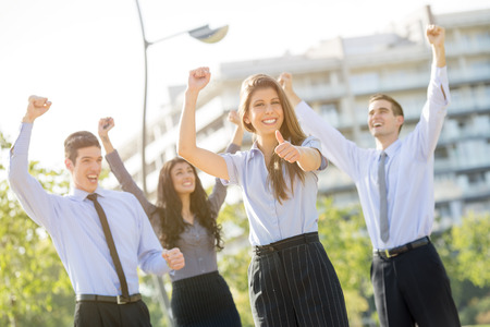 global partnership: Young businesswoman elegantly dressed with his team celebrating business success at a park near his office building Stock Photo