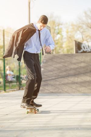Young businessman, elegantly dressed, holding a jacket draped over shoulder standing on a skateboard. photo