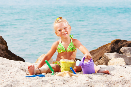 Heppy Little girl playing on the beach with bucket and spade photo