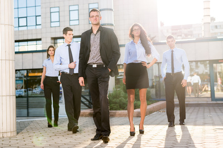 Young businessman, elegantly dressed with his hand in his pocket, standing proudly with his team of young businesswomen and businessmen in front of office building illuminated backlit sun. photo