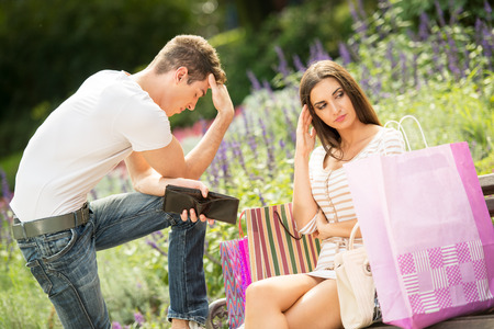 empty wallet: Young guy with an empty wallet in his hand with a worried expression on his face, stands leaning his girlfriend who sits on a park bench next to a bunch of shopping bags unhappy that her boyfriend does not have more money for shopping.