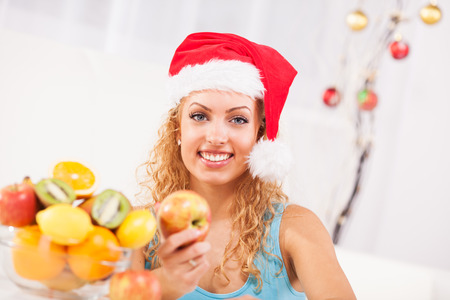 woman eating fruit: Beautiful young woman on New Years day  eat apple in her home with Santa Hat Stock Photo