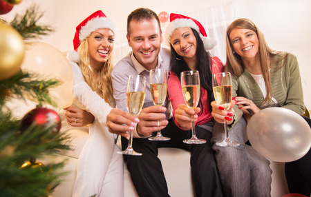 party room: Happy friends Celebrating Christmas or New Year with glass of champagne and toasting.