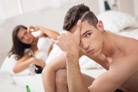decepci�n: Hombre joven con una expresi�n de decepci�n en su rostro, sentado en la cama junto mujer resaca acostado en una cama cubierto de botellas vac�as.