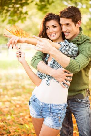 Joven pareja abrazada en los dedos extendidos del parque de la mano apuntando a algo, mientras que la niña lleva en la mano una ramita de hojas de otoño. Foto de archivo