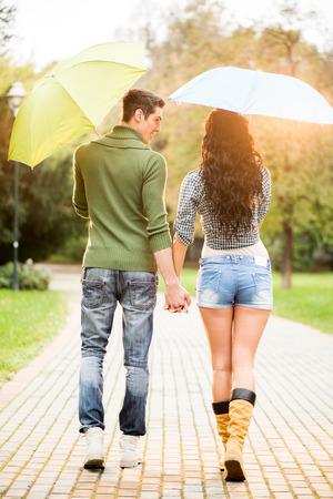 UOMO pioggia: Amare coppia, fotografati da dietro, a piedi attraverso il parco in una giornata piovosa mano e che trasportano gli ombrelli.