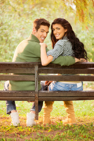 Photo of a young heterosexual couple hugging sitting on a park bench, behind their back looking at the camera with a smile on their faces.