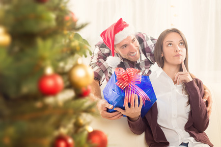 conceived: Young man gives his girlfriend a Christmas gift. She is conceived and looking up. Stock Photo