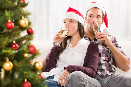 Young beautiful couple Celebrating Christmas or New Year with glass of champagne. photo