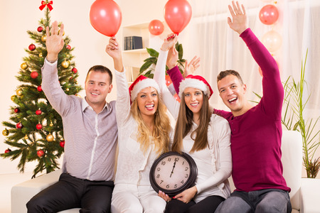 12 oclock: Happy friends Celebrating New Year in home interior with arms raised and showing midnight on the clock.