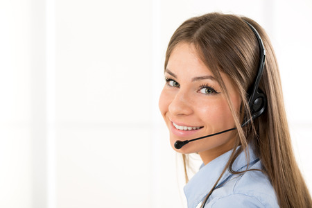 handsfree device: Young beautiful woman, call operator with headset smiling looking at the camera.