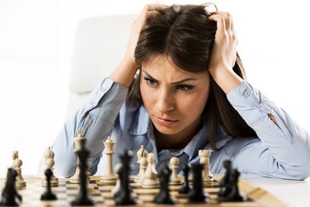 validez: Young preocup� empresaria delante de una mesa de ajedrez, sosteniendo sus manos a la cabeza mirando las piezas de ajedrez de preocuparse por la validez de sus movimientos.