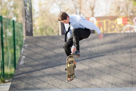 Young businessman, elegantly dressed, photographed at the moment of the jump with the skateboard at the skate park. Stock Photo