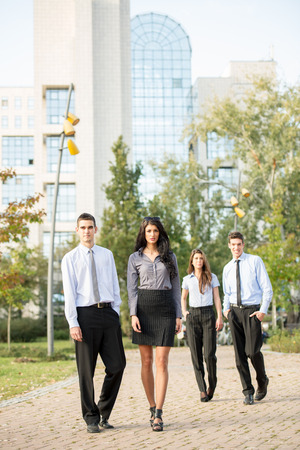 Group of young business people, formally dressed, walking through a park near their company. photo