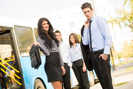 bus station: A small group of young business people elegantly dressed, standing at the bus station, waiting for a city bus which you can see in the background.