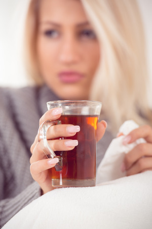 Close-up cup of tea held by the hand of girl, with a face out of focus, dressed in wool sweater,  tucked in a blanket.