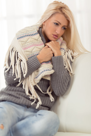 Beautiful blonde girl is sitting on the couch, dressed in a warm wool sweater, tucking a Shawl with a sad expression on her face. Stock Photo