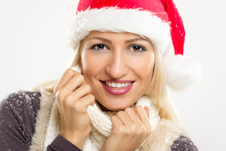 Close-up young beautiful blonde with a Santas cap on her head, covered in snow, smiling looks into the camera and tucking it into her scarf. Stock Photo