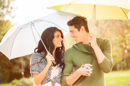 uomo sotto la pioggia: Giovane coppia eterosessuale a piedi nel parco per mano e che trasportano gli ombrelli. Archivio Fotografico