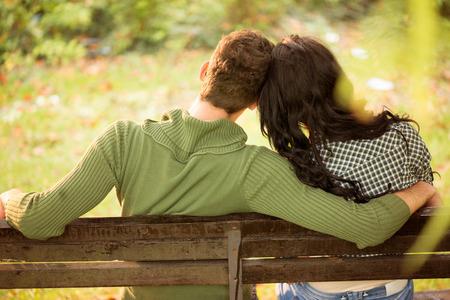 banc de parc: Photo d'un jeune couple, le dos tourn� � la cam�ra, assis sur un banc, la t�te pench�e sur l'autre.