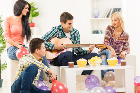 A small group of young people, friends at home party. A young man sitting on the couch between two beautiful girls, playing acoustic guitar and a guy sitting on the floor next to the stool photo