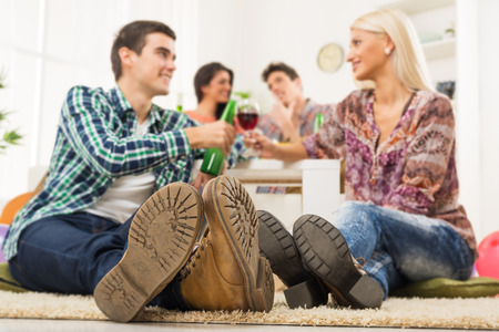 Young couple at house party with faces out of focus in the foreground are the soles of their shoes, sit on the floor, knocking the toasting glasses, in the background you can see another couple. photo