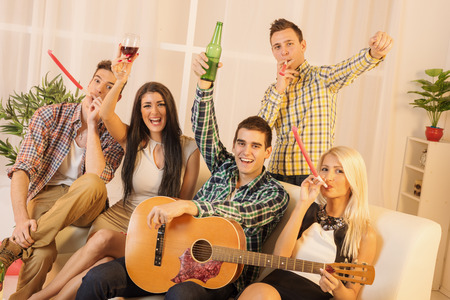 A small group of young people at home party smiling looking at camera. A guy with a guitar and a girl next to him toasting with drinks, and other companies in the entertainment blowing in party whistle. photo