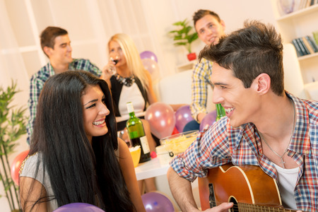 A young man with an acoustic guitar, at home party, courting a pretty girl playing to her. In the background you can see young people sitting on the couch and enjoy the atmosphere of home party. photo