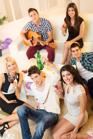 A small group of young people at home party, photographed from above, looking at camera smiling, enjoying the time together with music, drinks and snacks. photo