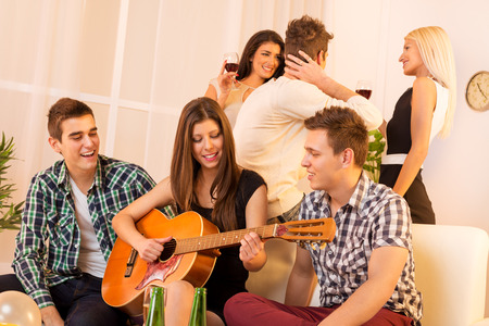 men friends: Girl playing acoustic guitar at house party, sit on the couch between two guys, and behind them is a guy who speak with two girls.