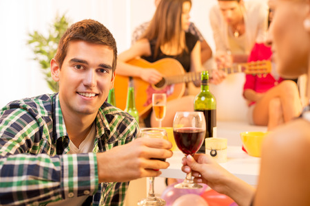 A young man with a glass of wine on the house party toast with a girl, and in the background you can see a group of young people gathered around the girl with an acoustic guitar. photo