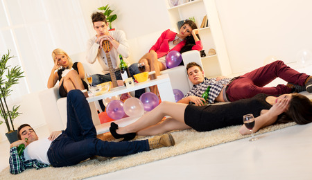 A group of young people, drunk and hungover after house party. A young man leaning on guitar, sitting on the couch between hungover girls. On the floor lay two boys and one girl. photo