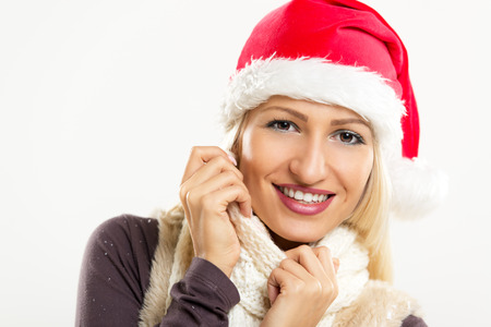 A young pretty blonde girl with Santas hat on her head, smiling looks into the camera and tucking it into her scarf.