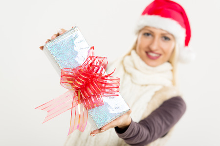 beautifully wrapped: Close-up beautifully wrapped gift with a decorative bow, holding a young pretty blonde girl with Santas hat. The girl is out of focus. Stock Photo