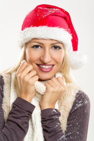 Young beautiful blonde with a Santas cap on her head, covered in snow, smiling looks into the camera and tucking it into her scarf.