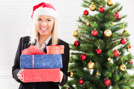 Happy Christmas businesswoman with Santa holding Christmas Presents. photo