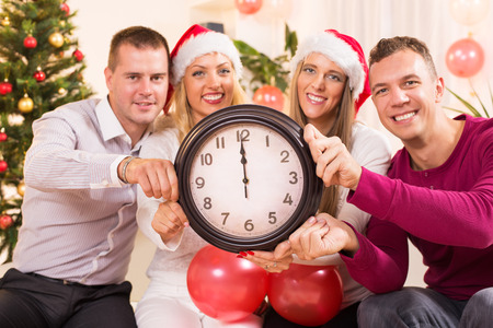 12 o'clock: Happy friends Celebrating New Year in home interior and showing midnight on the clock. Selective Focus, focus on the clock. Stock Photo