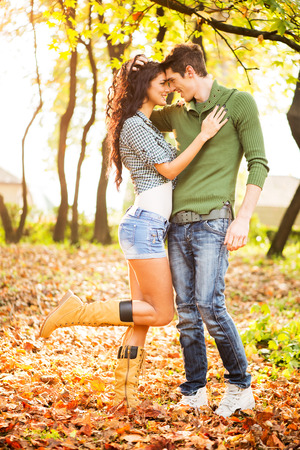 sexy boots: Young heterosexual couple in love in park, standing on fallen leaves, leaning their heads at each other, looking at each other and smiling.