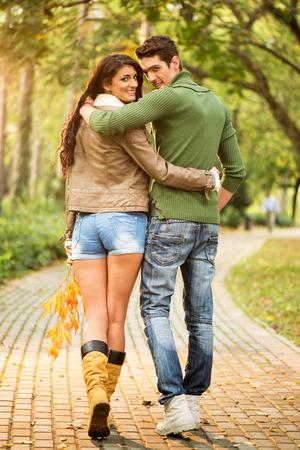 Joven pareja de enamorados abrazó caminar en los senderos en el parque mirando detrás de la cámara con una sonrisa en sus rostros.